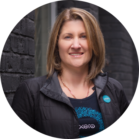 Woman wearing a Xero shirt standing in front of a brick wall